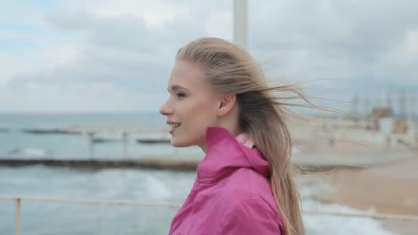 Dívka v kabátě chůzi po molu během bouře