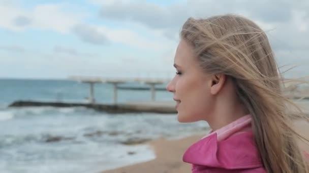 Blonďatá dívka vyvolává ruce nahoru na pláži