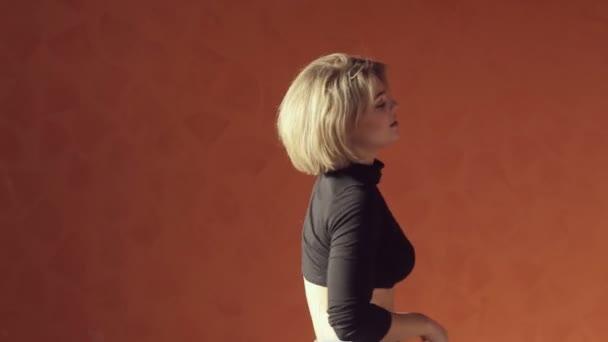 Energetic blond woman in short top and tights dancing twerk