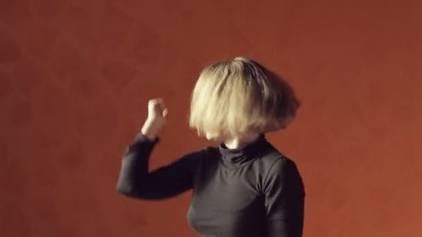 Vigorous blond woman in a short top and tights dancing twerk