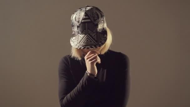 Sexy žena v čepici a šortky vrtěl její kořist a tance twerk