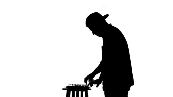 Black silhouette of a DJ playing a mixer on a white ...