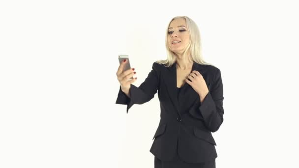 Sexy business woman in a jacket making selfie photo on a mobile phone on a white background