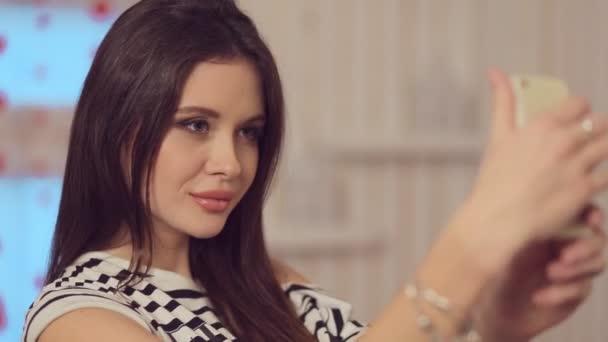 Krásná dívka s plné rty a make-up dělá selfie na telefonu s květinou ve vlasech