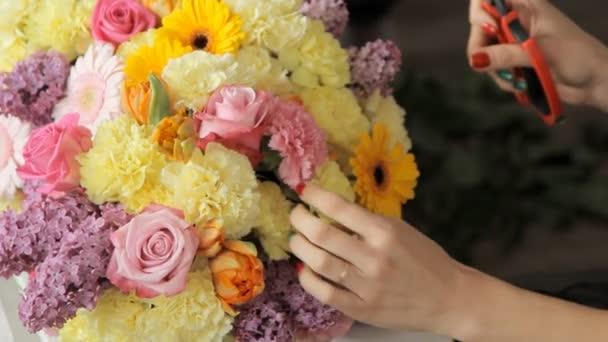 Moderní květinářství klade bledě žluté karafiáty v kytici tulipánů, šeříky, růže a další barevné květiny