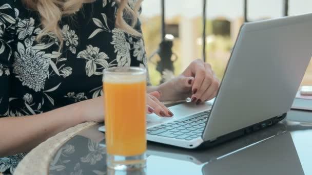 Gyönyörű szőke gépelés-ra egy laptop a kávézóban, a nyári teraszon