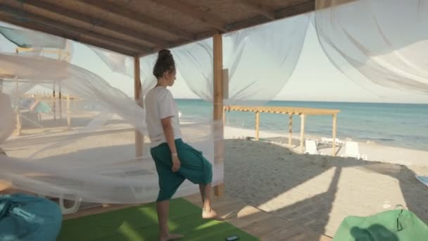 Mladá žena, která dělá cvičení u moře