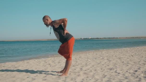Člověk dělá jógu na pobřeží pláže