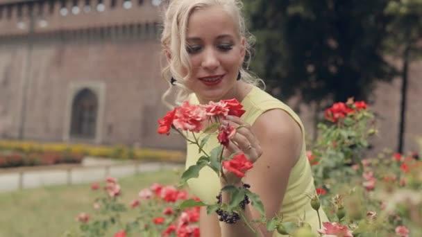 Krásná blondýnka ve žlutých šatech představující stojící vedle keřů kvetoucích růží v Miláně