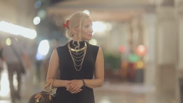 Atraktivní blondýna na vysokých podpatcích a oblečeni v dlouhých černých šatech chodí večer v Miláně