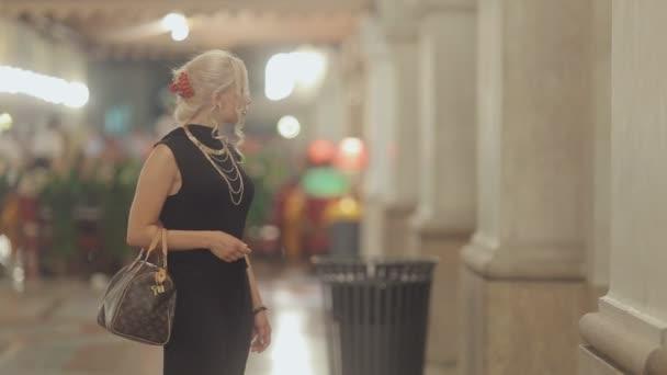 Elegant blondýna na vysokých podpatcích a oblečeni v dlouhých černých šatech uvažovat vitríny v Miláně večer