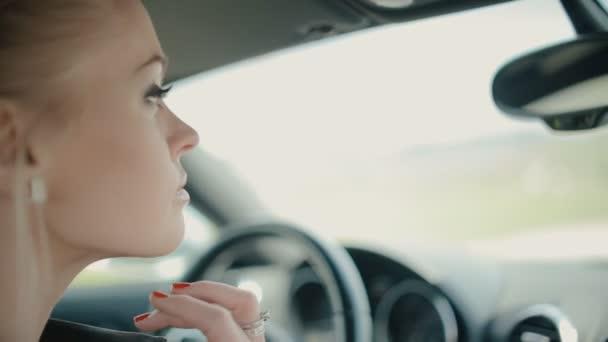 Modrooký žena dívá do zrcadla v autě