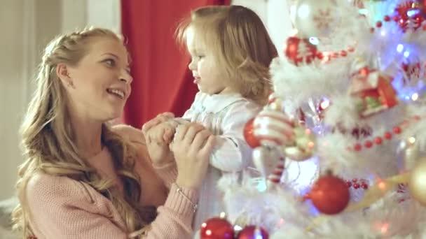 Matka s roztomilé dítě baví a líbat navzájem na vánoční stromeček doma