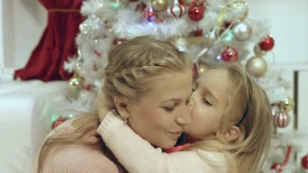Tochter umarmen und küssen ihre Mutter in der Nähe von Weihnachtsbaum