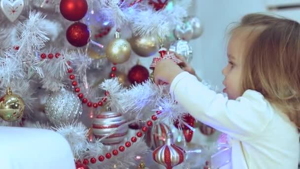 Malá holčička se dívá na světlé vánoční ozdoby