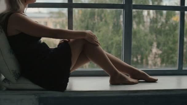 sexy Blondine sitzt auf einem Fensterbrett