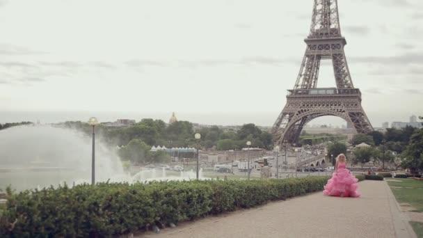 Dívka v nádherné dlouhé růžové šaty z Eiffelovy věže