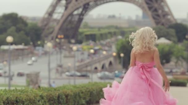 Dívka v nádherné růžové šaty dlouho běží poblíž Eifellova věž