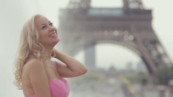 Laughing girl dressed in a pink strapless dress near the Eiffel Tower