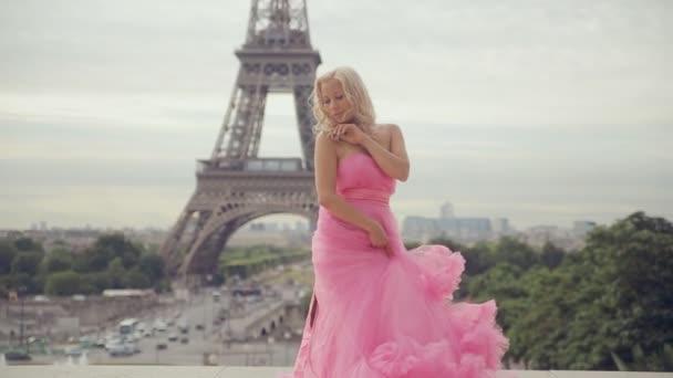 Nabídka dívka v dlouhé šaty růžová víla pózuje v blízkosti Eiffelovy věže v Paříži