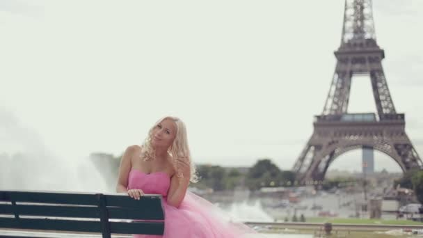 Fancy žena v slavnostní šaty sedí na lavičce s výhledem na Eiffelovu věž