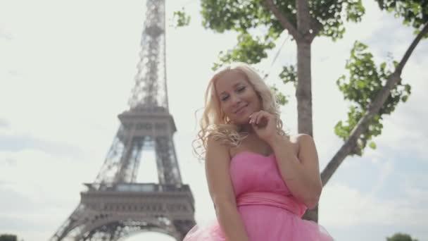 Krásná blondýna oblečená v slavnostní růžových šatech sedí poblíž Eifellova věž