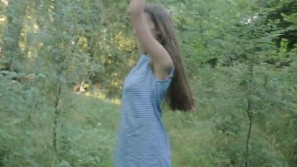 Mladá žena jde vpřed podél cest v lese