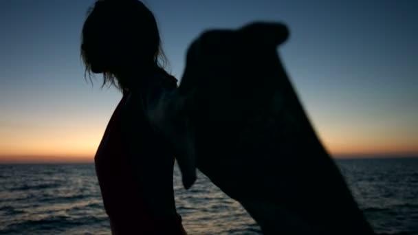 Sziluettje vékony fiatal nő naplementekor