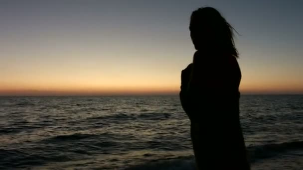 Silhouette of girl at sunset on the sea