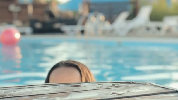 Lovely girl dressed in bikini leaned her elbows on the edge of the wooden pier in a pool