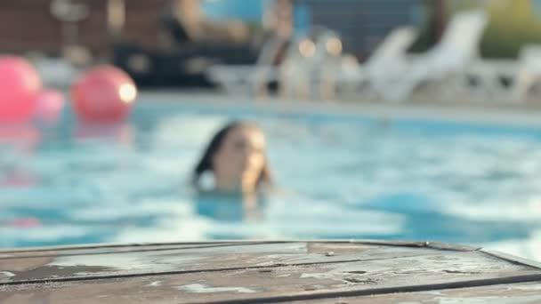 Gyönyörű barna szemű lány, hosszú hajú viselt bikini úszás a medencében, és ferde a könyökét egy fából készült mólón