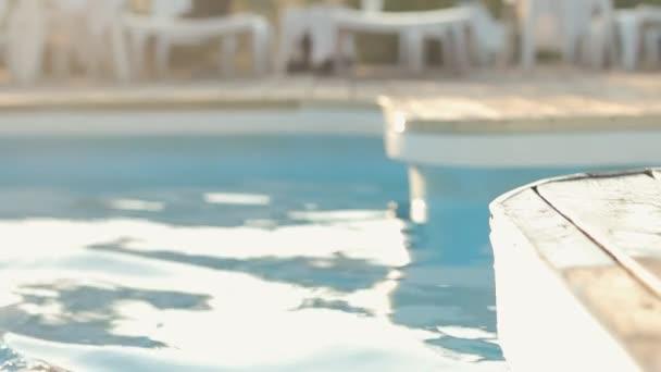 Krásná bruneta v bikinách, které sedí v bazénu a pózní