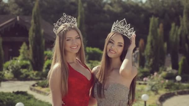 Two beautiful young girls in crowns and evening dresses posing in a green park
