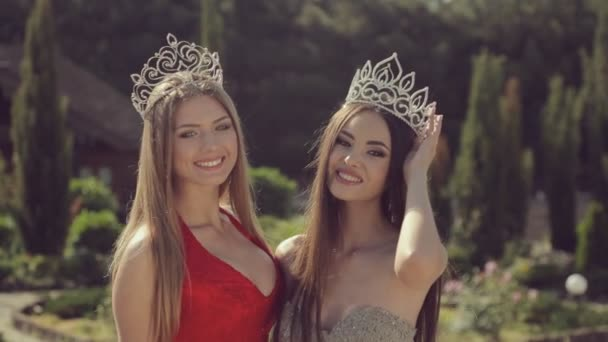 Two charming young girls in evening gowns and crowns smiling and posing in  green park