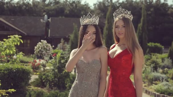 Two sexy young girls in evening gowns and crowns smiling and posing in a green park