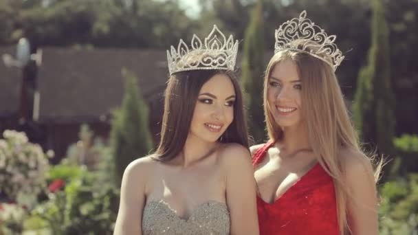 Two wonderful long-haired beauties in crowns standing in a summer garden