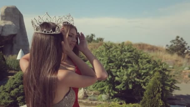 Two young women with long hair and the expensive crowns on their heads smiling while standing in a garden