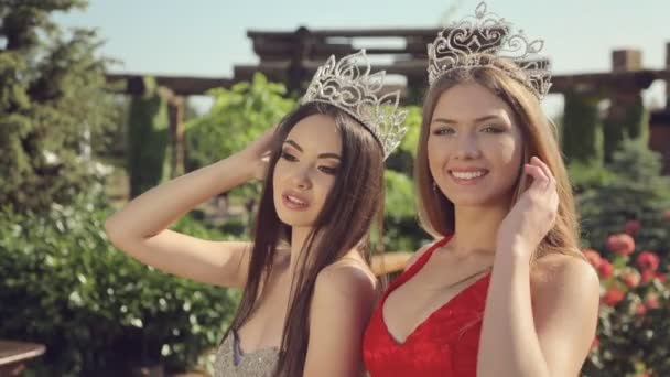 Two young beauty contest winner in long evening dresses and crowns in the garden with roses