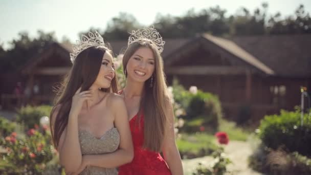 Two amazing girls in a long gowns and crowns laughing in the park with roses