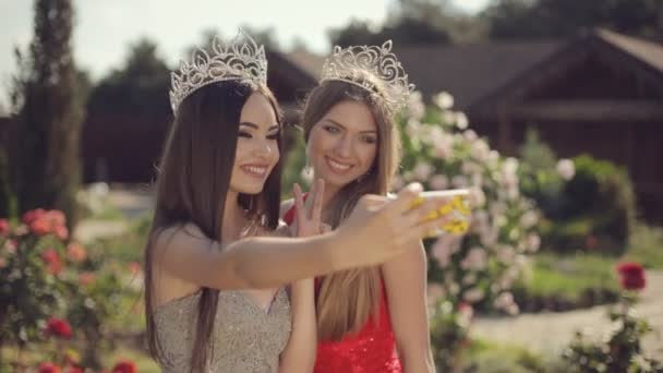 Two charming girls in evening gowns and crowns laughing and doing phone selfie in a garden with roses