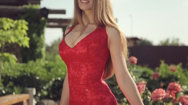 Portrait of a cute girl in a long red dress with a beautiful bust in a park with flowers