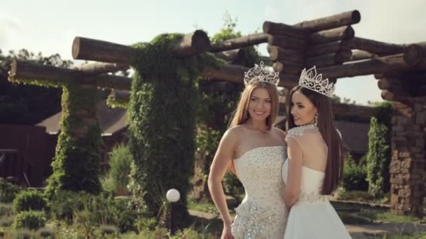 Portrait of two girls in wedding dresses and crowns outdoors in a park