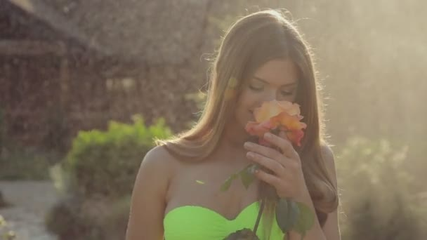 Incredibly cute girl with long hair wearing a bikini standing with a beautiful rose in the garden under spray of water