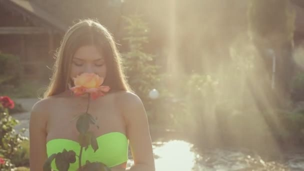 Incredibly cute girl with long hair wearing in bikini sniffing a beautiful rose in the garden under a spray of water