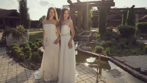 Attractive girl in expensive wedding dresses posing in a magical garden