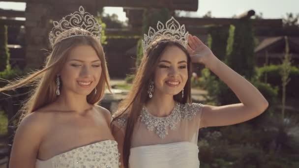 Mosolygó lányok a drága menyasszonyi ruhák és tiaras pózol egy varázslatos kertben