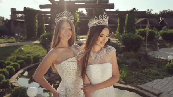 Charming girls in crown and white wedding dress posing and smiling in the park