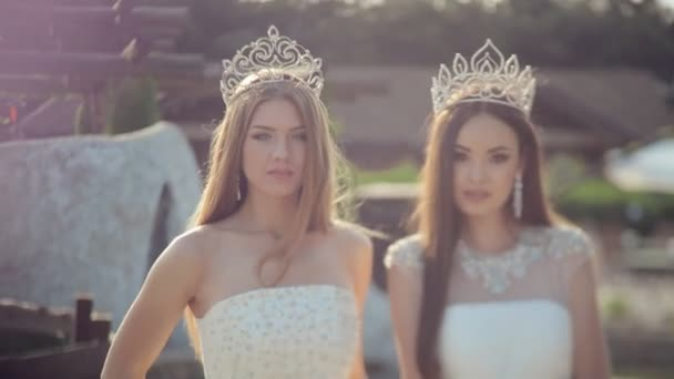 Charming girls in the white gowns embroidered with stones and the crowns on the head outdoors