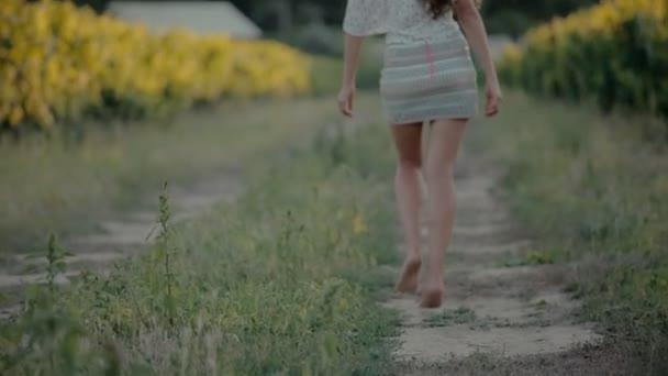 Moderně oblečená dívka v krátké sukni chodí podél vinic