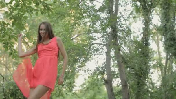 Šťastná dívka v zářivě růžových šatech, stojící na skále uprostřed řeky